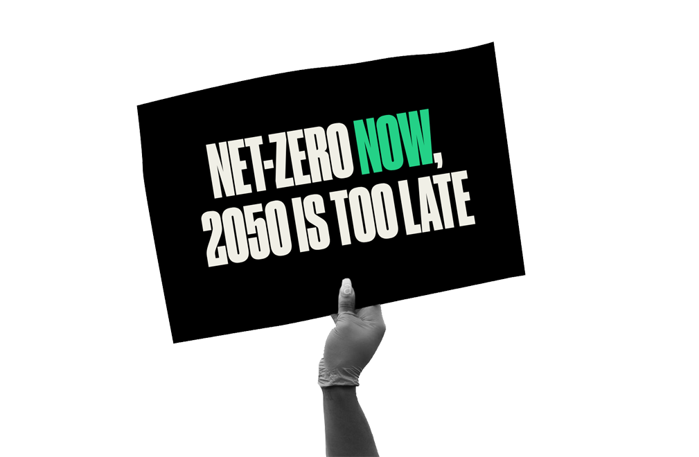 Hand holding sign reading 'Net-zero now. 2050 is too late.'