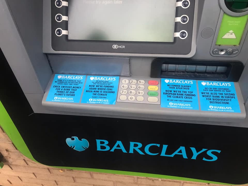 Protest stickers on a Barclays cash macine